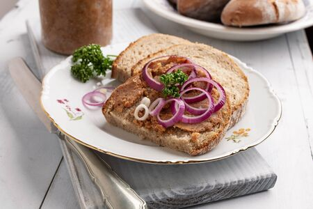Bread with pork lard mixed with ground cracklings, decorated with purple onion rings and parsley Stock Photo