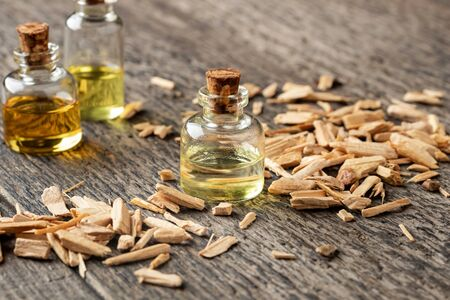 Bottles of essential oil with cedar wood chips on a table