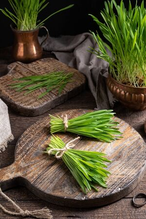 Two bundles of fresh barley grass on a rustic wooden table