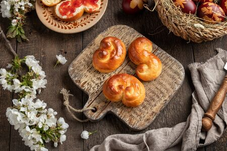 Jidasky or jidase - Czech sweet Easter pastry made of yeast dough, with eggs dyed with onion peels in the background