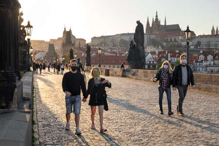 PRAGUE, CZECH REPUBLIC - APRIL 16, 2020: Half-empty Charles Bridge during the coronavirus pandemic, with people walking in protective face masks