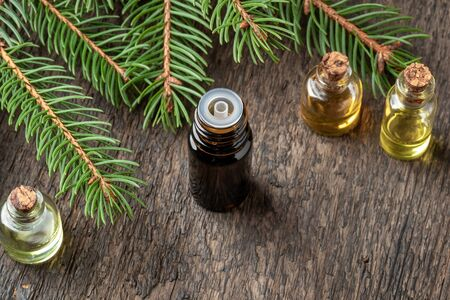 A dark bottle of essential oil with spruce branches Imagens