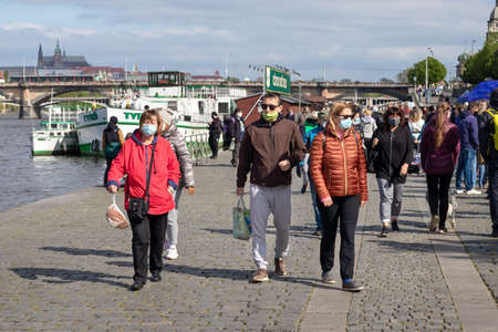 PRAGUE, CZECH REPUBLIC - APRIL 25, 2020: People shopping at the re-opened Naplavka farmers market, wearing protective face masks because of the coronavirus pandemic Editorial