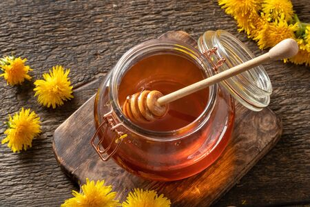 Honey dipper in a jar of dandelion syrup Imagens