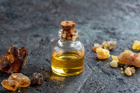 A bottle of frankincense essential oil on a dark background