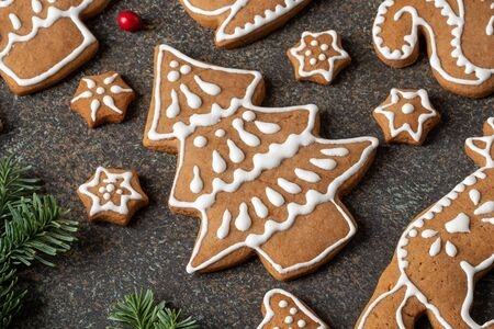 Tree shaped and other Christmas gingerbread cookies on a dark background