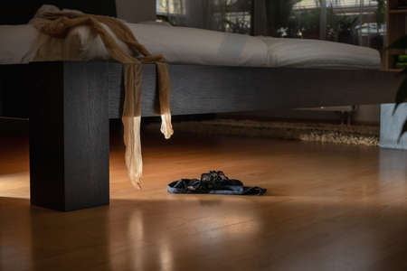 Black panties lying on the floor and stockings hanging from a bed in a dark room