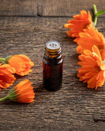 A bottle of essential oil with calendula flowers on a wooden background Reklamní fotografie
