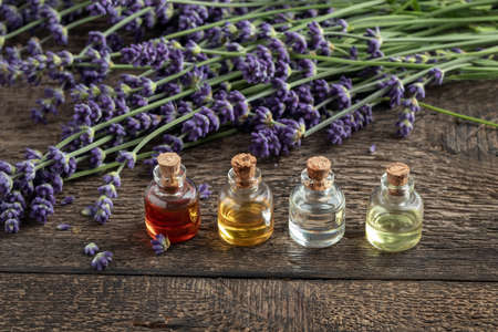 Bottles of essential oil with fresh blooming lavender on a wooden table