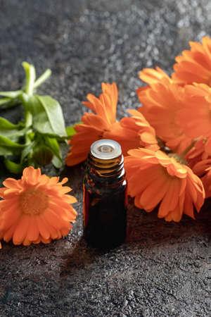 A dark bottle of essential oil with fresh calendula flowers Standard-Bild