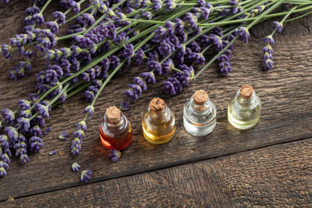 Bottles of essential oil with fresh lavender flowers