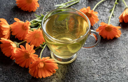 A cup of herbal tea with calendula flowers Standard-Bild