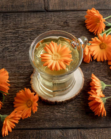 Calendula tea with fresh flowers on a wooden table