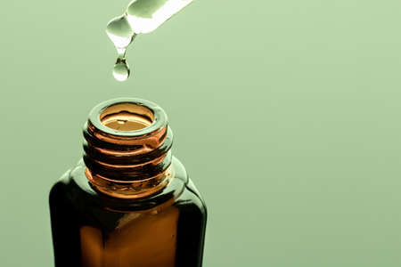 A bottle of essential oil with a dropper on a green background