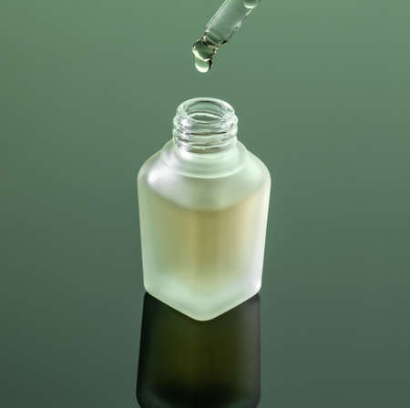 A bottle of essential oil with a drop falling into it