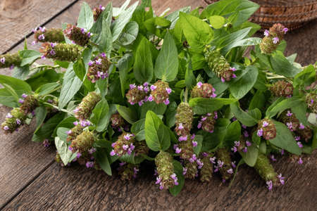 Fresh blooming common self-heal, or Prunella vulgaris twigs on a wooden table