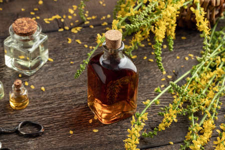 A bottle of herbal tincture with fresh blooming agrimony