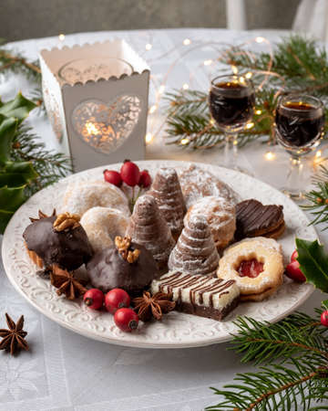Beehives, Linzer and other Christmas cookies arranged on a plate on a table, with nut liqueur in the background