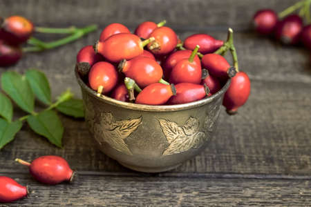 A bowl with fresh rosehips on a table Standard-Bild