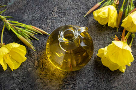 A bottle of evening primrose oil with fresh Oenothera biennis flowers