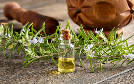 A bottle of essential oil with blooming rosemary twigs