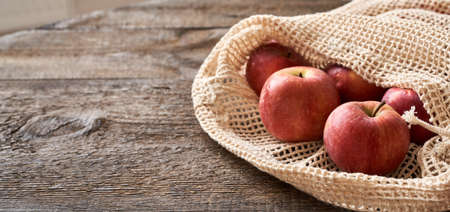 Fresh apples in an ecological reusable mesh bag made of organic cotton, with copy space