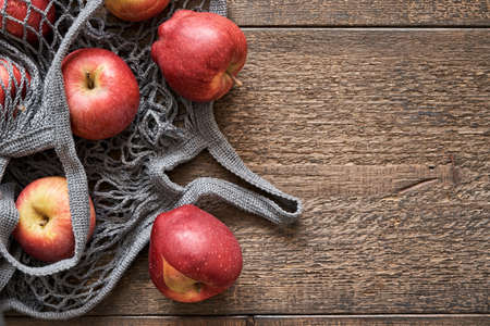 Fresh red apples in a stretch bag on a wooden background, top view with copy space