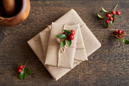 Fresh wintergreen twigs on Christmas presents wrapped in ecological recycled paper, top view