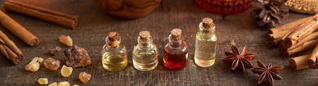 Panoramic header of essential oil bottles with frankincense and Christmas spices - star anise and cinnamon