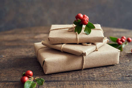 Christmas presents wrapped in ecological recycled paper with wintergreen twigs on a table