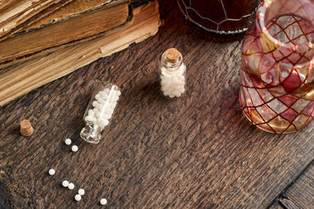 A bottle of homeopathic pills spilled on a wooden table, with vintage books in the background Reklamní fotografie