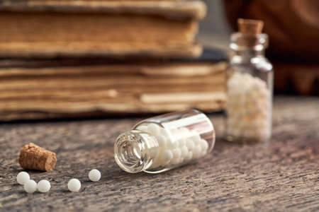 A bottle of homeopathic pills on a wooden background, with vintage books in the background