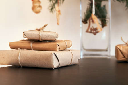 Christmas presents wrapped in ecological recycled paper with wooden and straw decoration in the background Reklamní fotografie