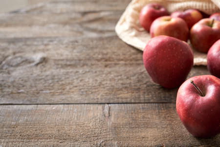 Red apples on a table, with an ecological reusable mesh bag made of organic cotton in the background, with copy space