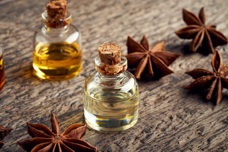 A bottle of essential oil with star anise on a table