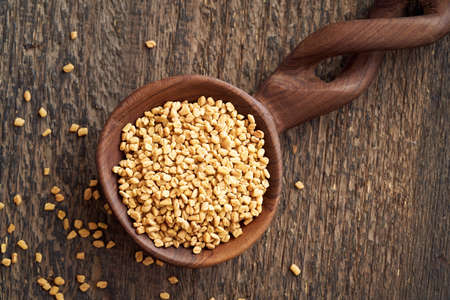 Fenugreek seeds on a wooden spoon on a table