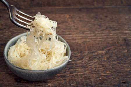 Fermented cabbage on a fork, with copy space