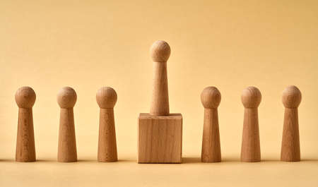 One wooden figure standing higher than others - concept of leadership or winning