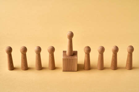 Wooden figure standing on a pedestal higher than others - concept of leadership or winning, with copy space