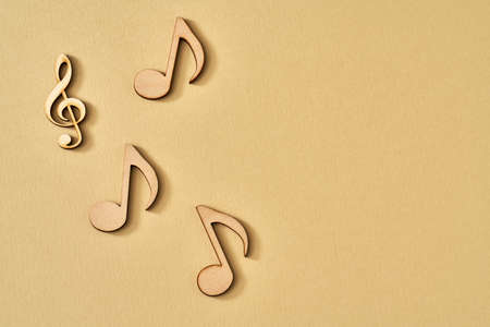 Wooden musical notes on yellow background, top view with copy space