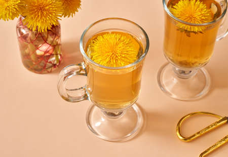 Herbal tea with fresh dandelion flowers on a pastel orange background