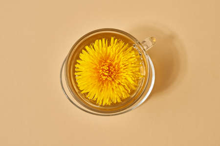 A cup of dandelion tea on pastel beige background, top view