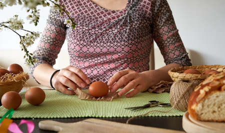 Woman preparing Easter eggs for dyeing with onion peels at home, with flowers and mazanec pastry in the foreground