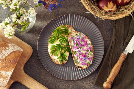 Slices of Sourdough bread with ground elder leaves, lungwort and other wild edible spring plants