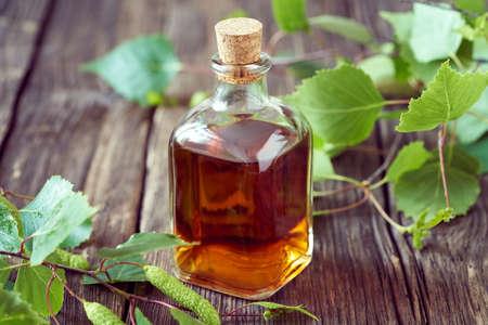 A transparent bottle of homemade herbal tincture with fresh birch branches Standard-Bild