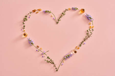 Heart shape with essential oil bottles, frankincense, lavender and thyme, with copy space Standard-Bild