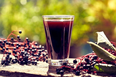 A glass of homemade black elder syrup with fresh elderberries, outdoors in sunlight