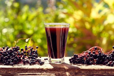 A glass of black elderberry syrup - alternative herbal remedy