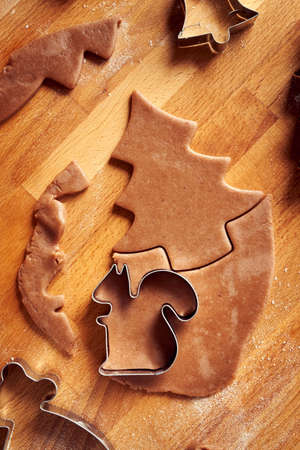 Cutting out animal and tree shapes from rolled out dough to prepare homemade gingerbread Christmas cookies
