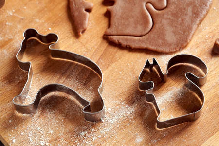 Biscuit cutters and pastry dough ready to prepare homemade Christmas gingerbread cookies